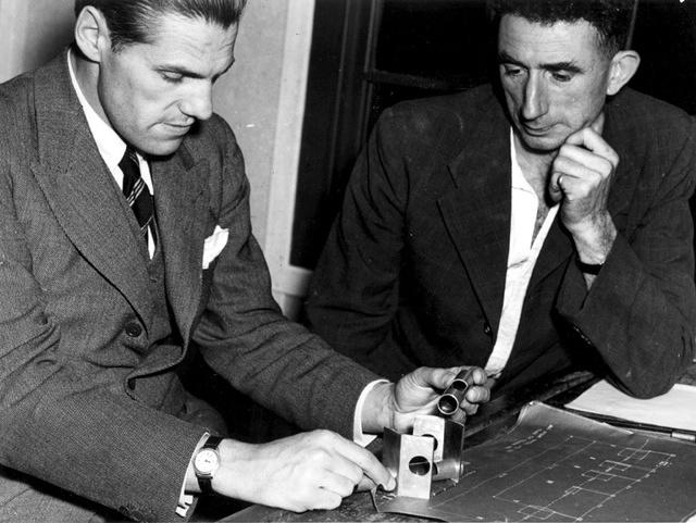 Richard Woolley and Jim Banham inspecting optical and mechanical components, optical munitions factory, 1944