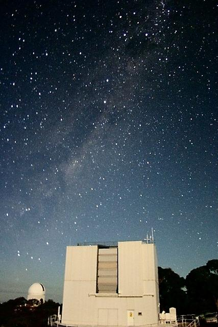 Looking south-east at the moonlit ANU 2.3m telescope building with the Anglo-Australian Telescope dome in the distance